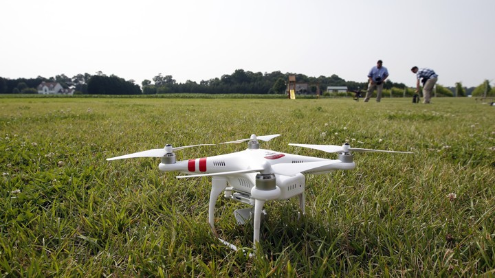 A DJI Phantom 2 drone sits on grass.