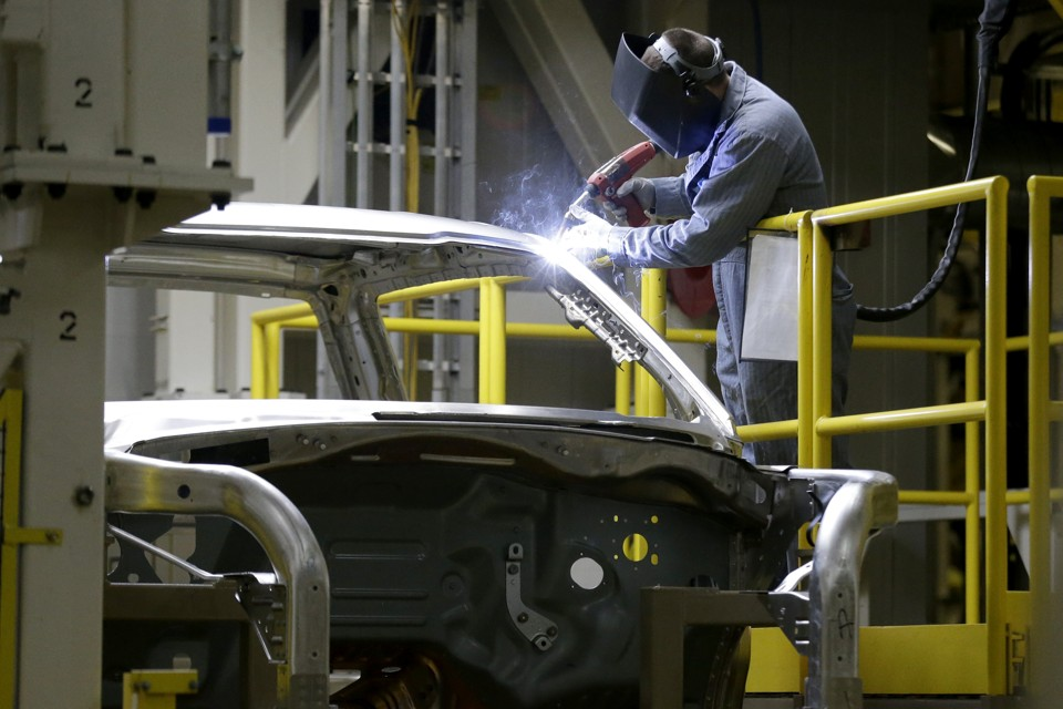An auto worker works on a car.