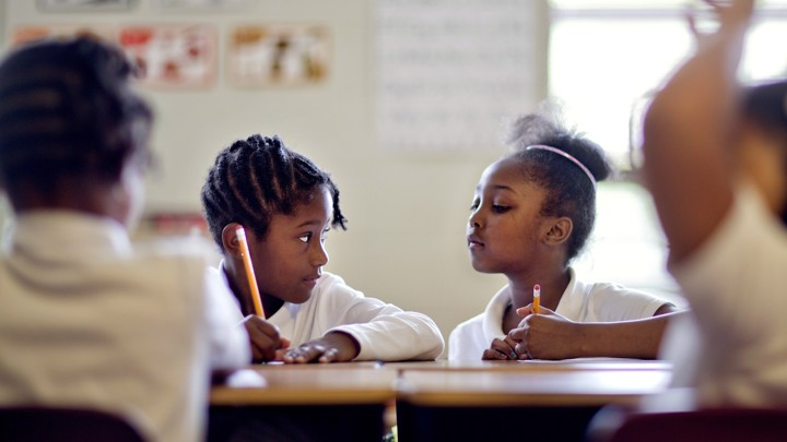 """A student looks at another's worksheet. The other student gazes at her skeptically, as if to say, """"You're kidding, right?"""""""