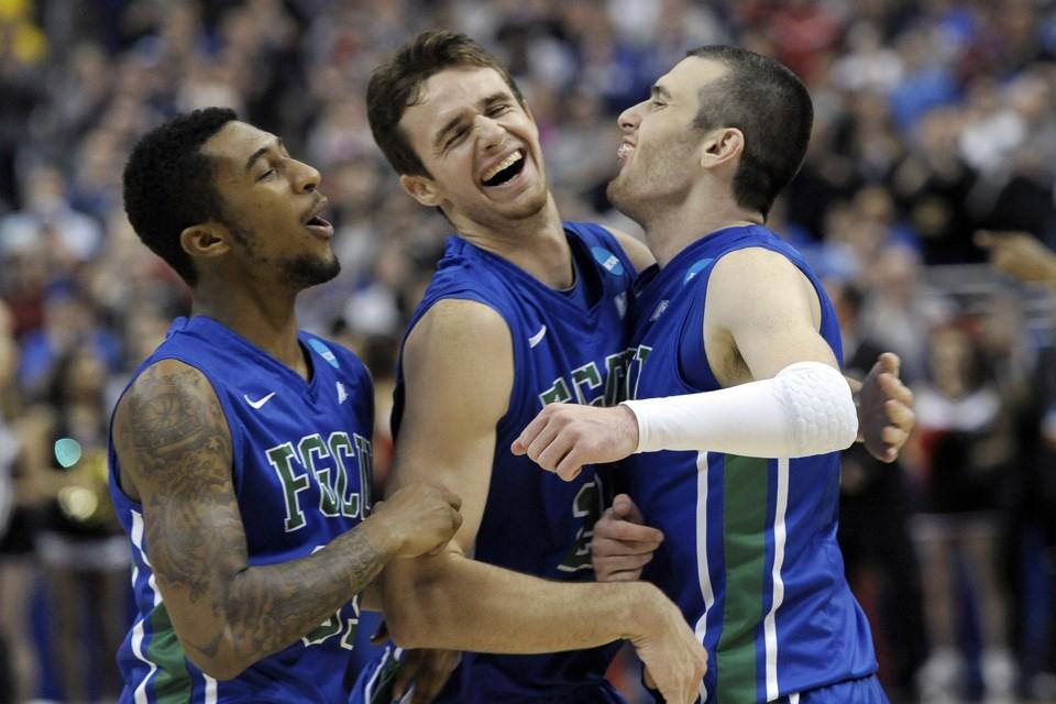 Three basketball players hug and smile