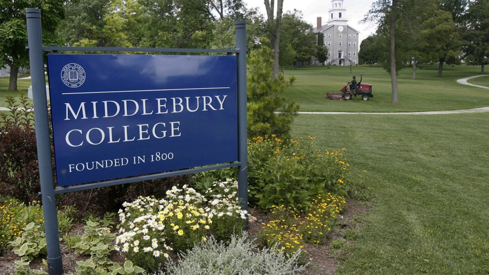 "A sign reads ""Middlebury College, founded in 1800."" A lush green lawn with a tractor fills the rest of the photo."
