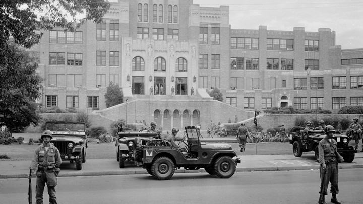 This black and white photo shows men in combat attire standing guard outside a large brick school building. Three military-esque Jeeps are in the photo.