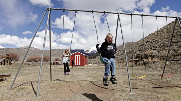 Two children play on the swings outside a red schoolhouse. The setting is rural.