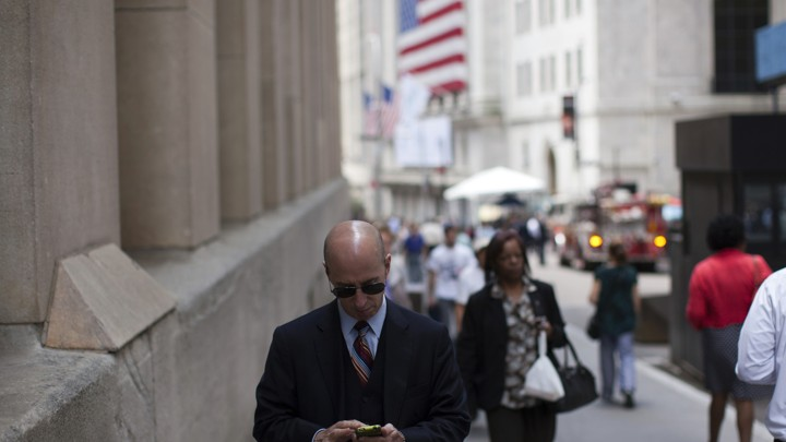 A man checks his phone while walking down a busy street