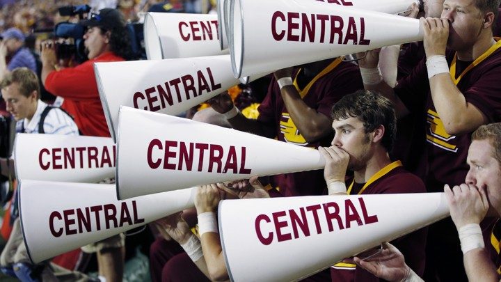 "People hold megaphones that read ""CENTRAL"" along the side in the stands of a football game."