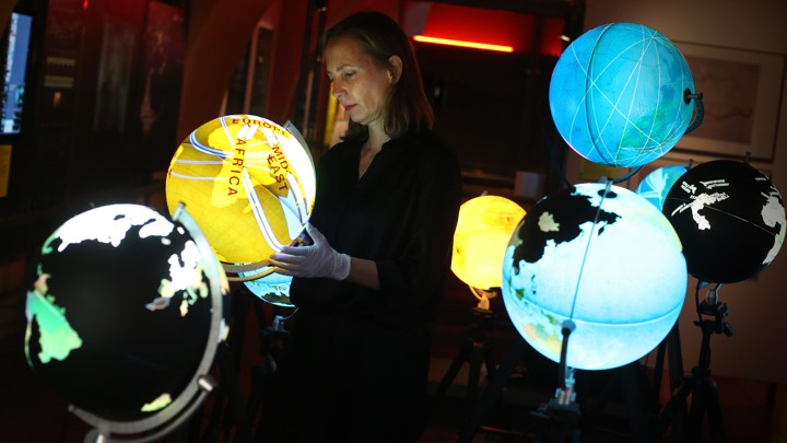 Curator Olga Subiros checks Ingo Gunther's Worldprocessor globes visualizing world data at the Big Bang Data exhibition at Somerset House on December 2, 2015, in London, England.