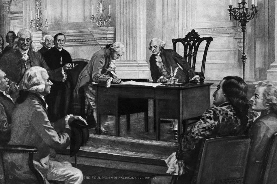 George Washington watches from his desk as a delegate signs the Constitution.