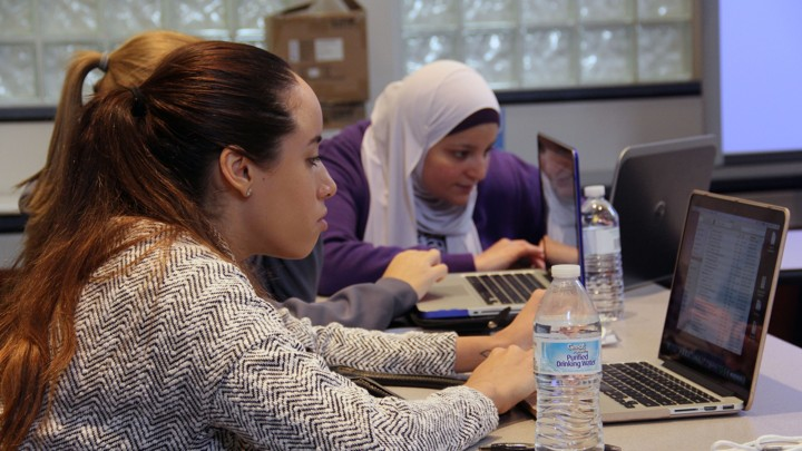 Students sit at laptop computers