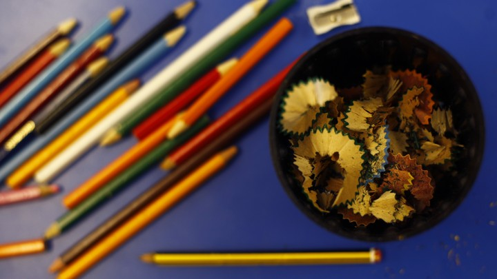 Colored pencils alongside a sharpener and a bowl of shavings