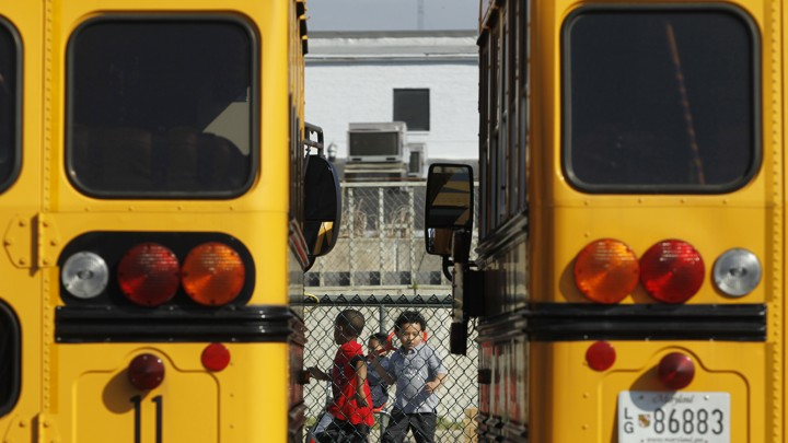 Preschool students play behind a fence. They are framed between two yellow school buses.