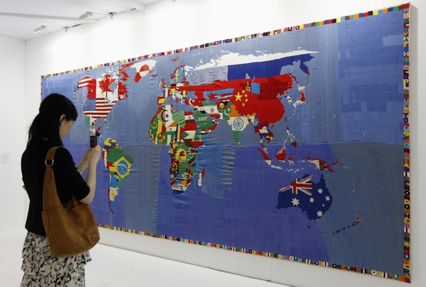 A woman takes a photo of a map. The countries' flags fill their borders in the representation.