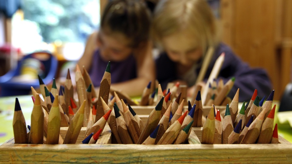 Two children draw with colored pencils