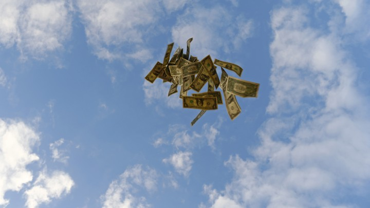 Dollar bills float against a blue sky