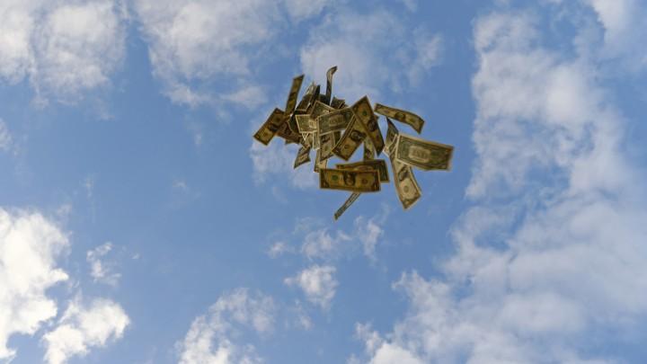 Dollar bills float against a blue sky