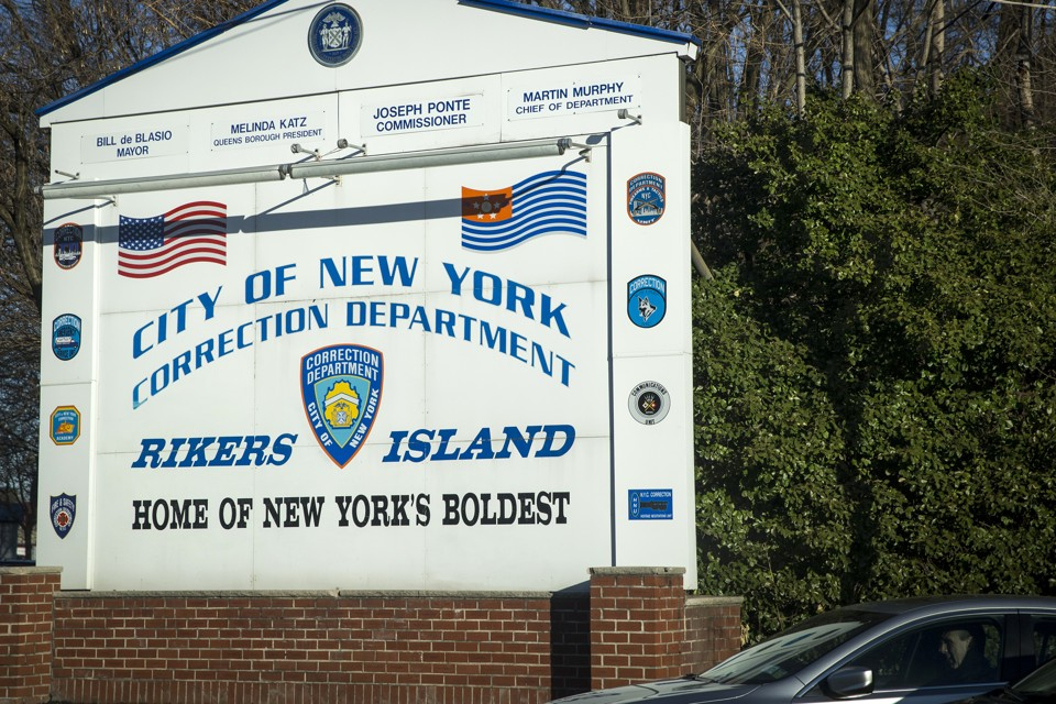 "A sign reading ""City of New York Correction Department: Rikers Island, Home of New York's Boldest"""