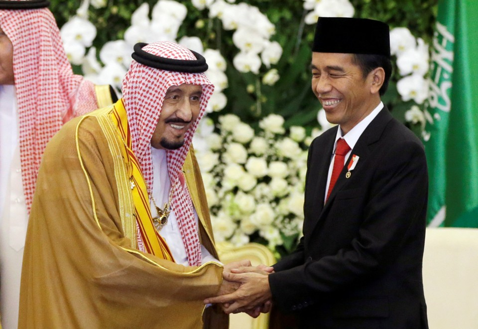Saudi King Salman shakes hands with Indonesian President Joko Widodo.