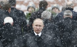 Russian President Vladimir Putin stands in the snow at a wreath laying ceremony.