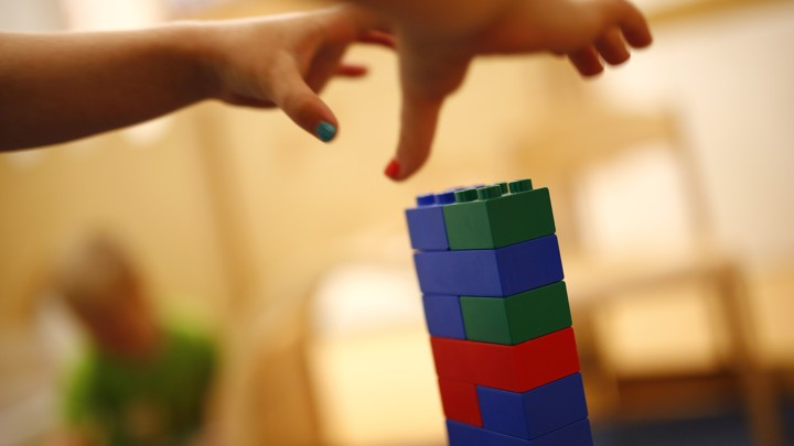 Two children's hands grab for a tower of LEGOs.
