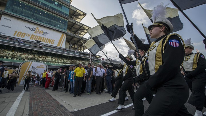 Students in black and gold marching-band uniforms hold Purdue flags and walk in tandem.