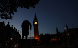 Dawn breaks behind the Houses of Parliament and the statue of Winston Churchill in Westminster, London, on June 24, 2016.