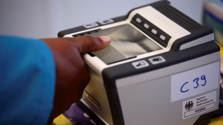 A woman places her thumb on a fingerprint scanner.