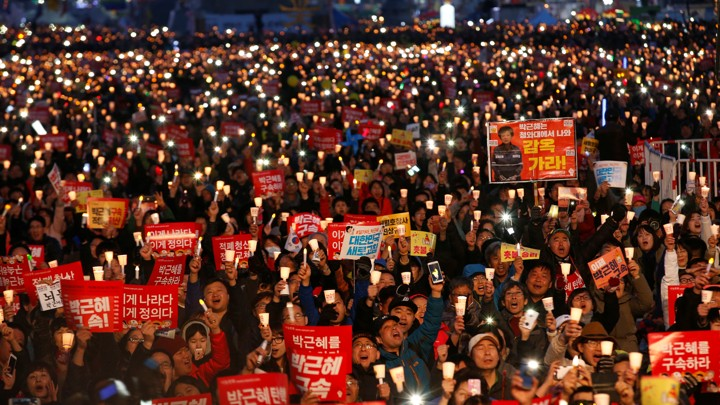Protesters hold candles as they celebrate the impeachment of South Korea's ousted leader Park Geun Hye.