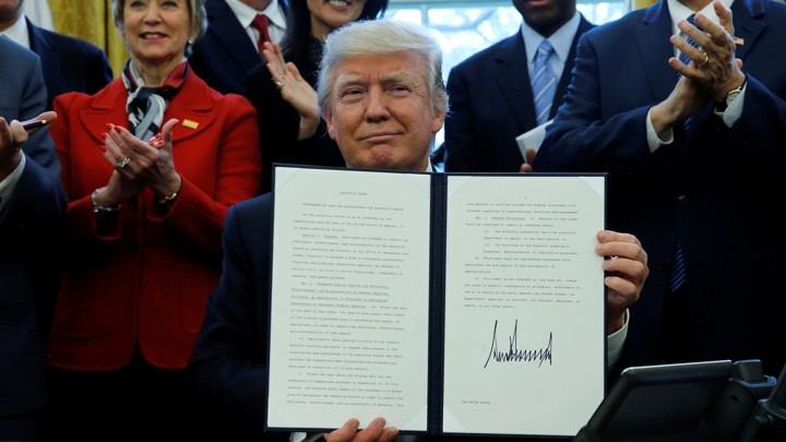 President Donald Trump holds a signed copy of an executive order