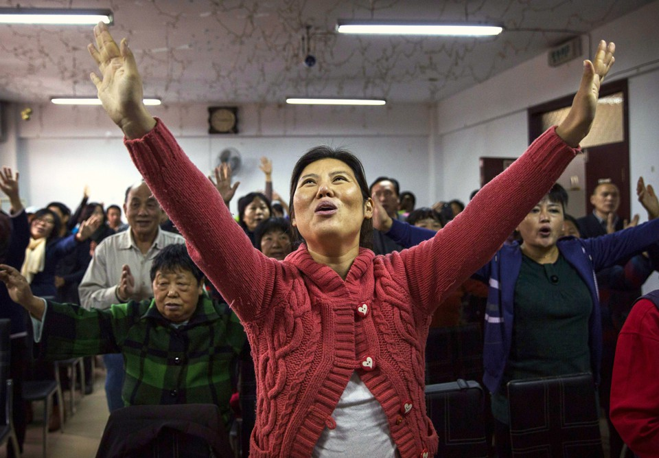 A Chinese Christian woman sings during a prayer service at an underground Protestant church in Beijing. A Chinese Christian woman sings during a prayer service at an underground Protestant church in Beijing