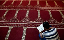A Muslim faithful reads the Quran inside a makeshift mosque.