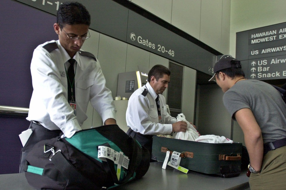 San Francisco International Airport security personnel search through a passenger's luggage.