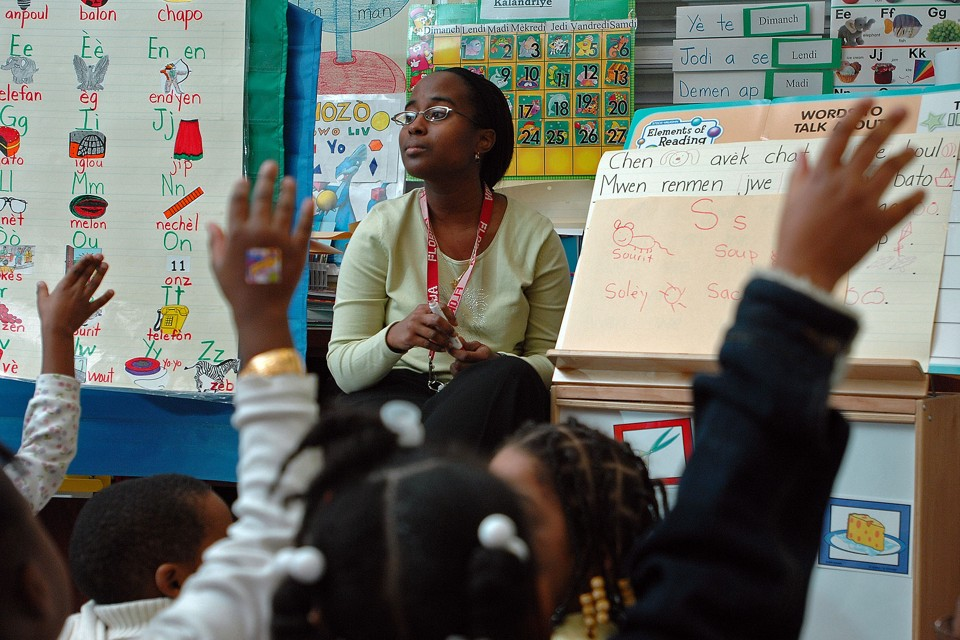 A teacher sits in front of her class. Students raise their hands.