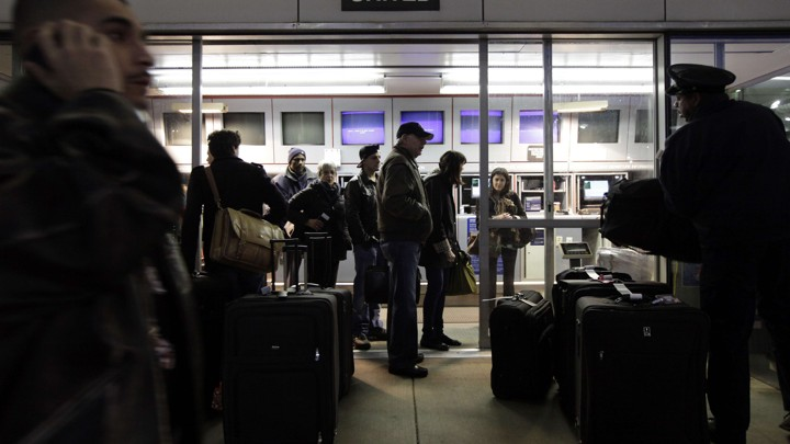 Travelers check their luggage at a United Airlines express check-in area at O'Hare International Airport in Chicago