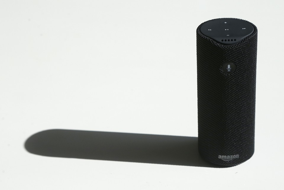 An Amazon Tap sits on a white tabletop.