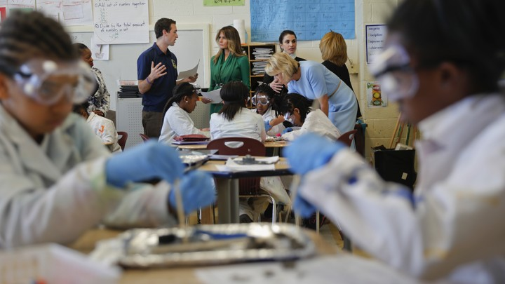 Melania Trump, Queen Rania, and Betsy Devos stand at the back of classroom while black students wearing goggles work on a science experiment.