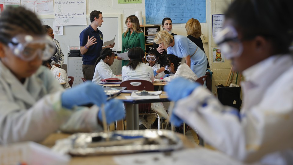 Melania Trump, Queen Rania, and Betsy Devos stand at the back of classroom  while