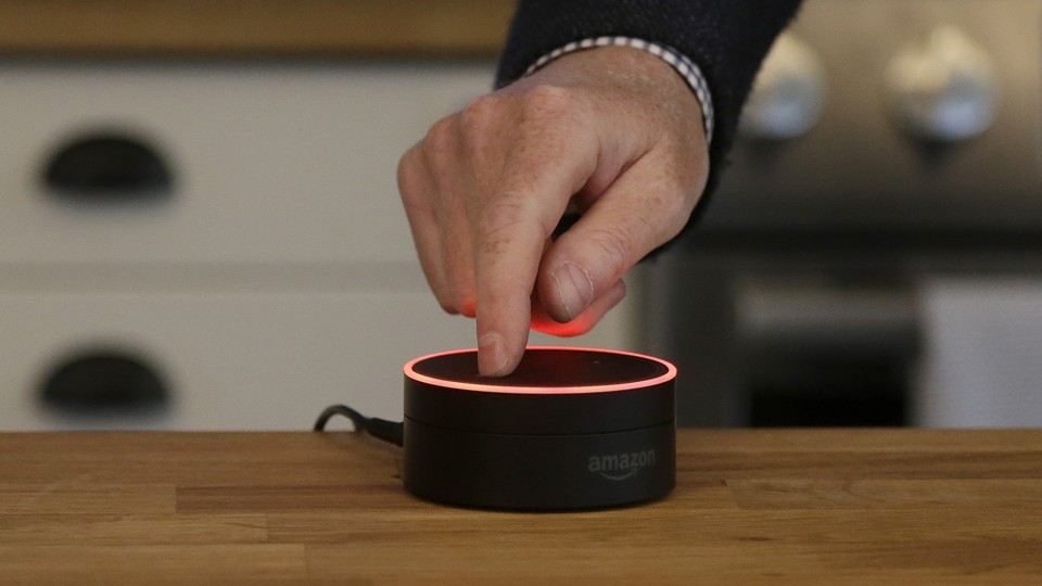 A man mutes an Amazon Echo Dot