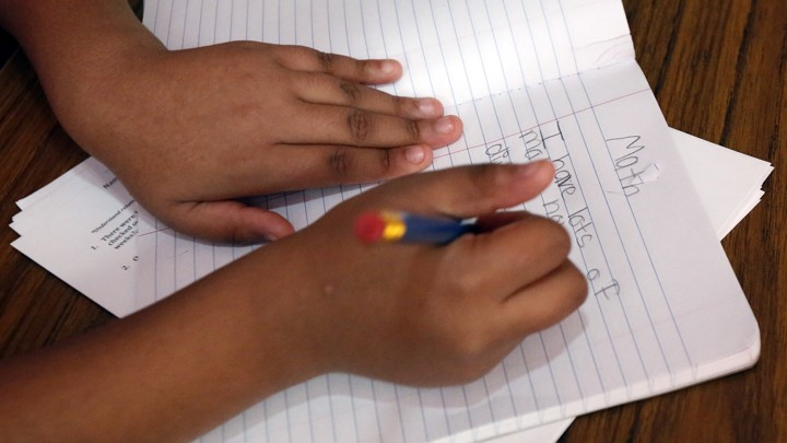 A child holds a pencil and writes on a sheet of notebook paper.