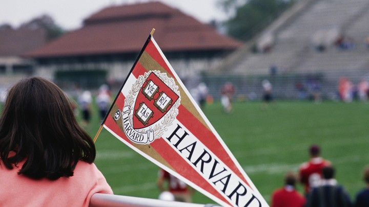 A girl holds a Harvard pennant.