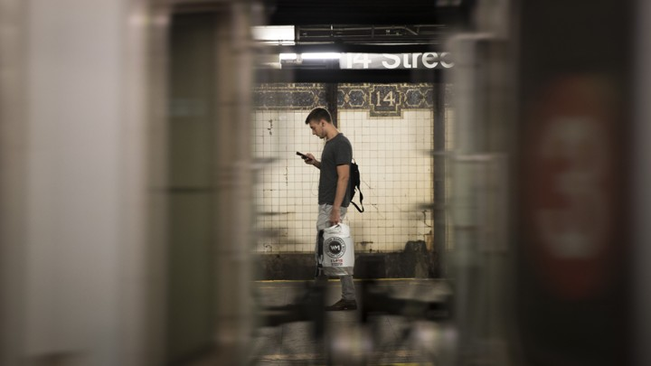 Seen between the cars of a passing train, a man looks at his phone on a subway platform.