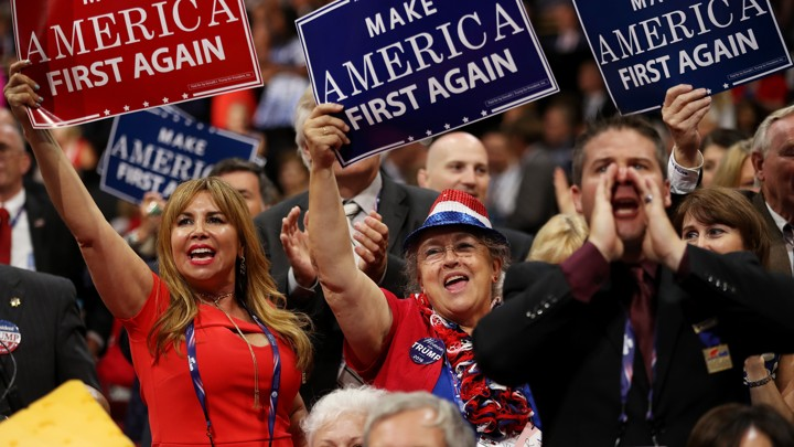 """Delegates hold up signs that read """"Make America First Again"""" during the opening of the third day of the Republican National Convention on July 20, 2016."""