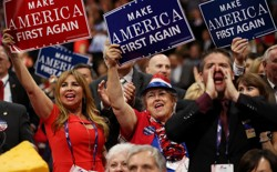 "Delegates hold up signs that read ""Make America First Again"" during the opening of the third day of the Republican National Convention on July 20, 2016."
