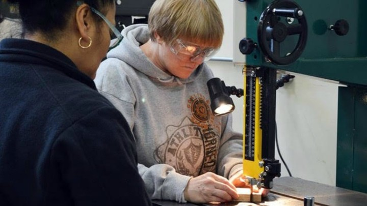 A woman in a sweatshirt and goggles moves a piece of wood through a machine.