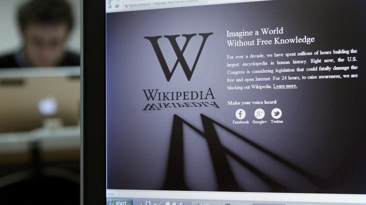 A reporter's laptop shows the Wikipedia blacked out opening page.