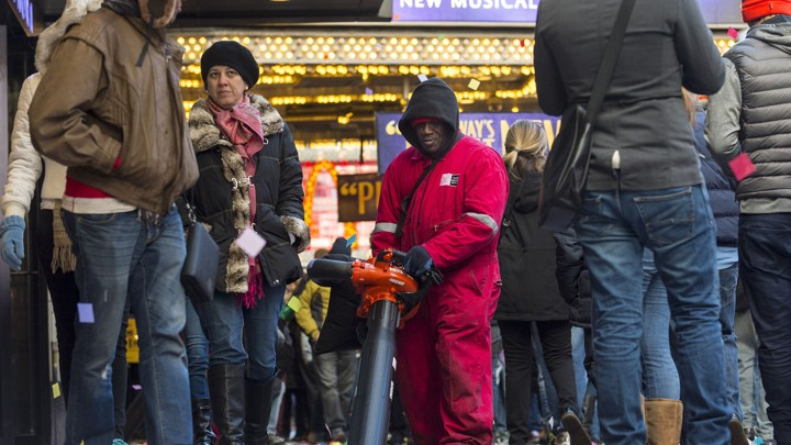 A man cleans up confetti while surrounded by tourists in Times Square in New York.