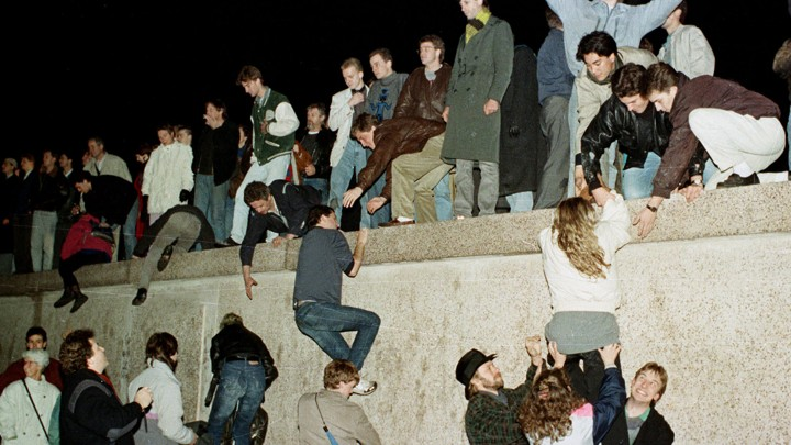 East German citizens climb the Berlin wall at the Brandenburg Gate as they celebrate the opening of the East German border on November 10, 1989.