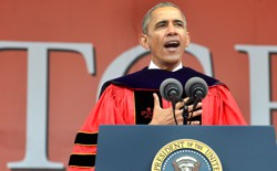 Barack Obama stands at a microphone wearing a graduation gown.