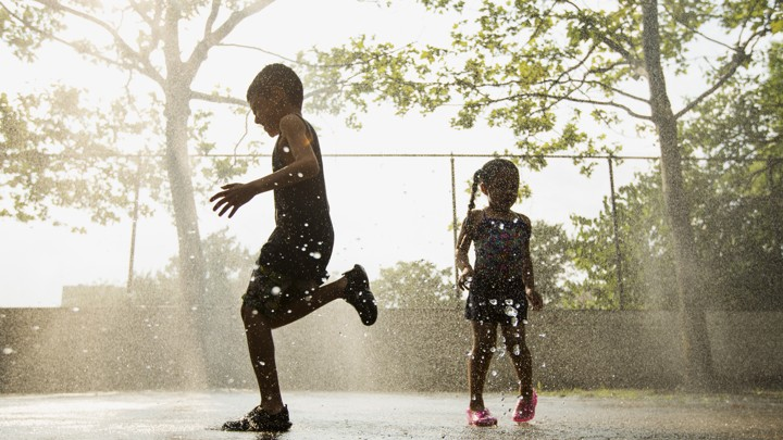 Silhouettes of children running through sprinkles