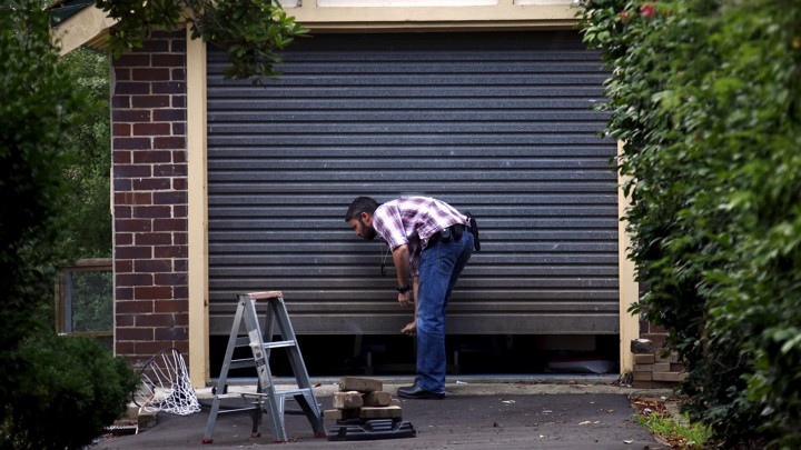 A man closes a garage door by hand.