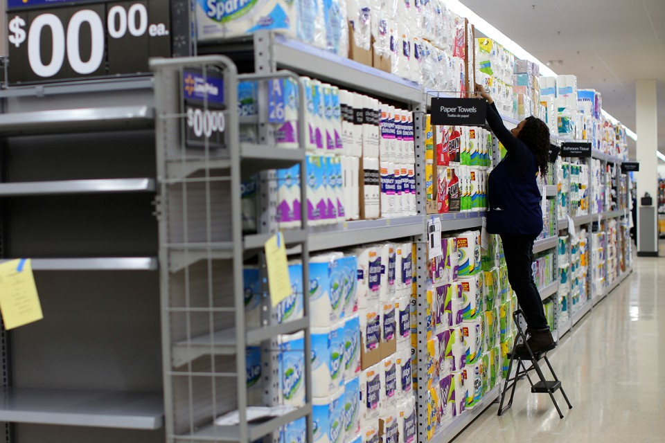 A Walmart employee stocks rolls of paper towels on a shelf.