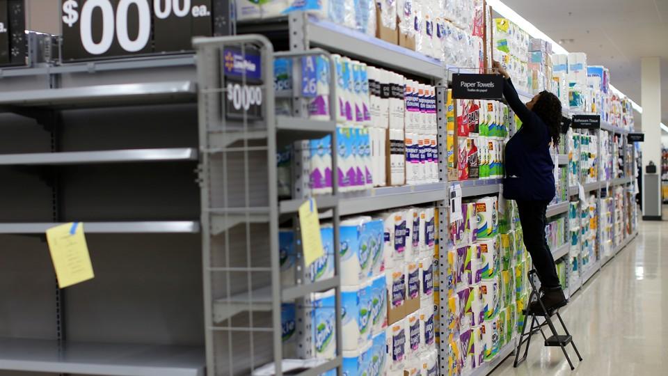 A Walmart employee stocks rolls of paper towels on a shelf.